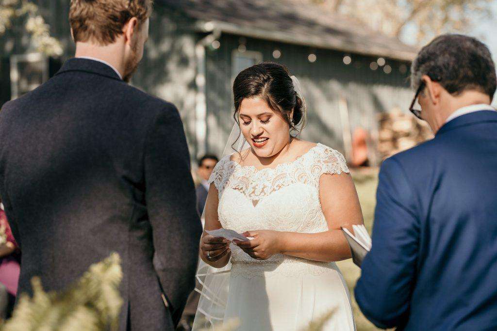 bride reads vows to groom during farm wedding ceremony