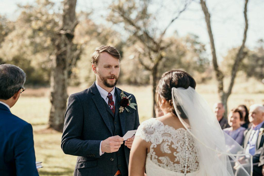 groom reads vows to bride at ceremony