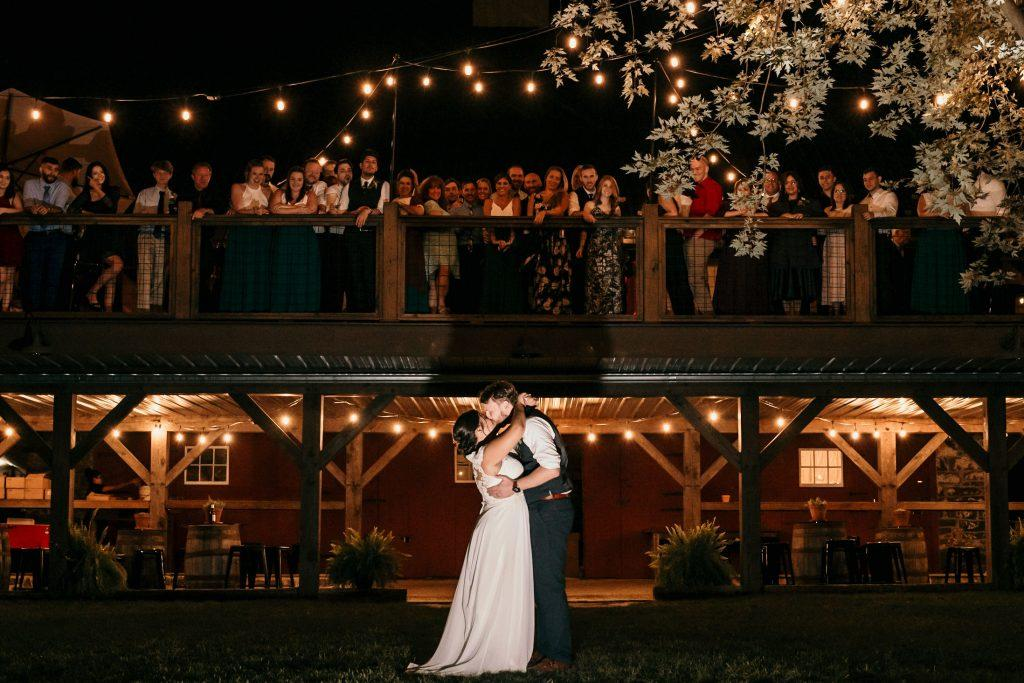 bride and groom kiss under the stars at farm wedding reception