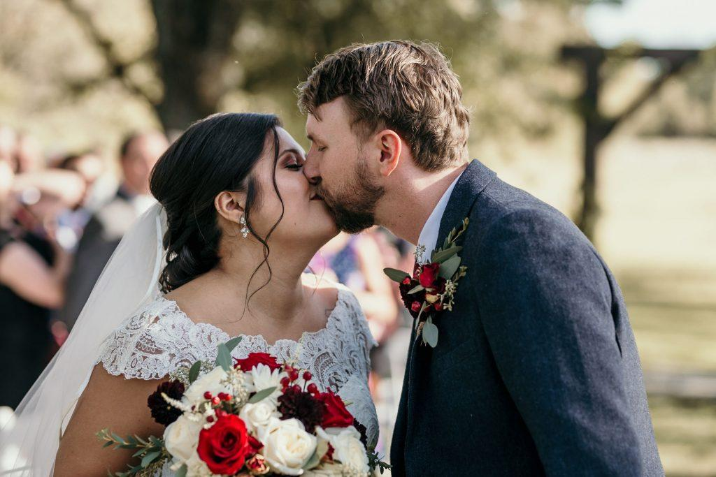 bride and groom kiss at farm wedding ceremony
