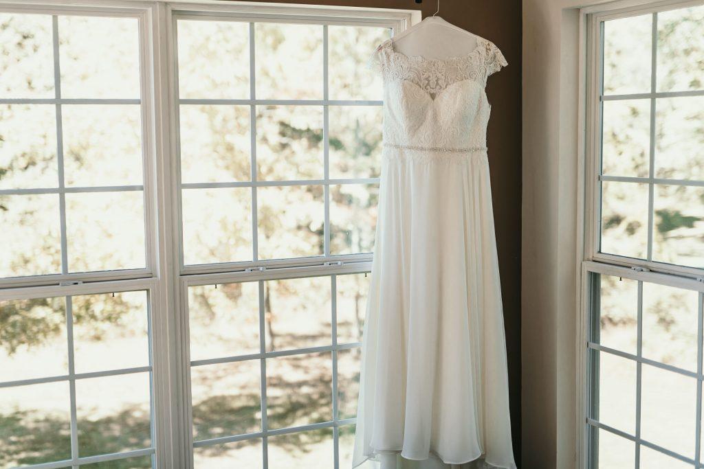wedding dress hanging by windows