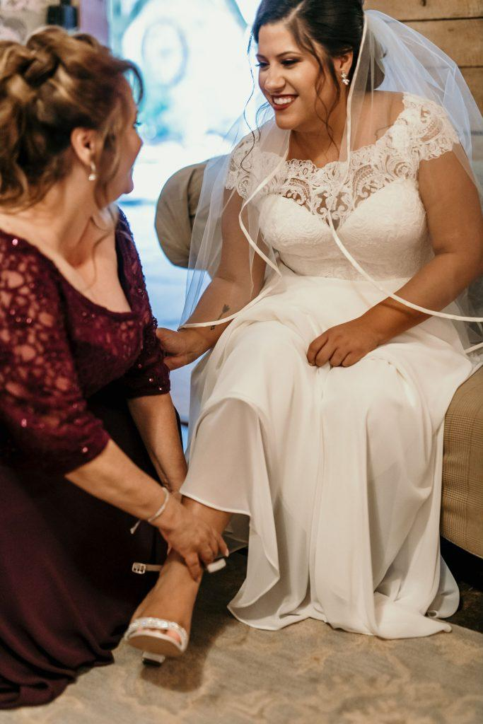 mother of the bride helps put bride's shoes on