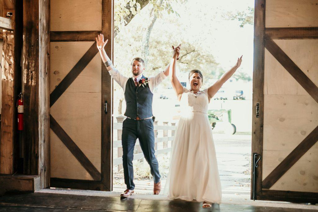 married couple entering into barn reception
