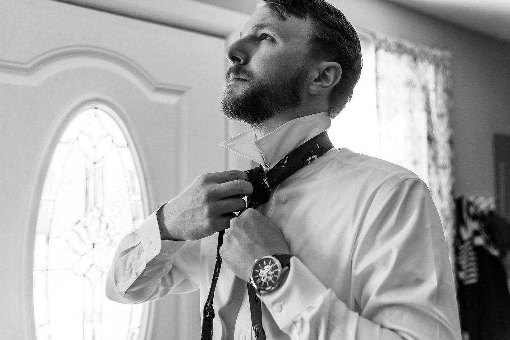 groom putting on tie on wedding day