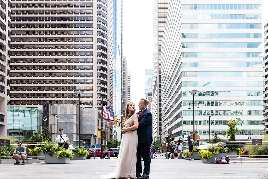 wedding couple embrace in front of buildings