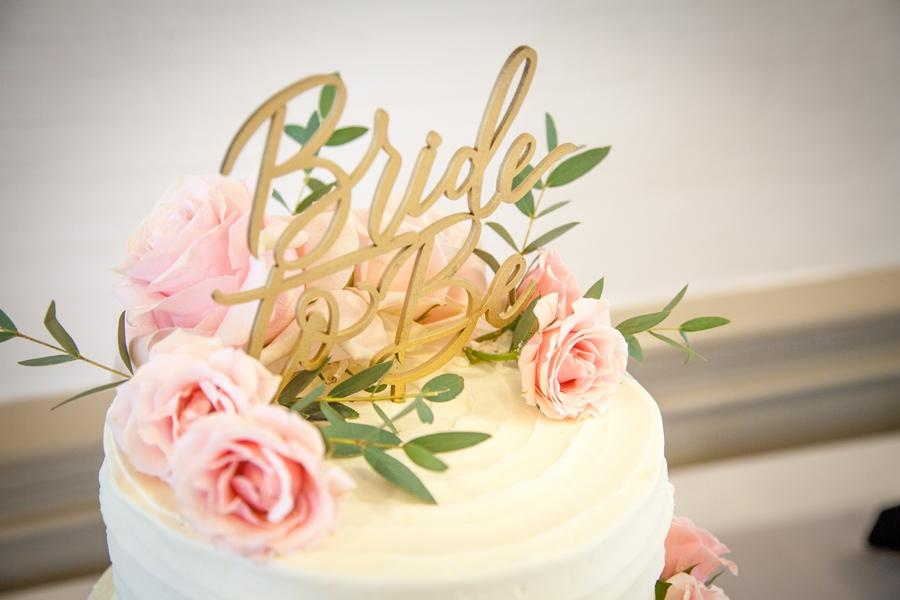 white frosted cake with bride to be topper and roses