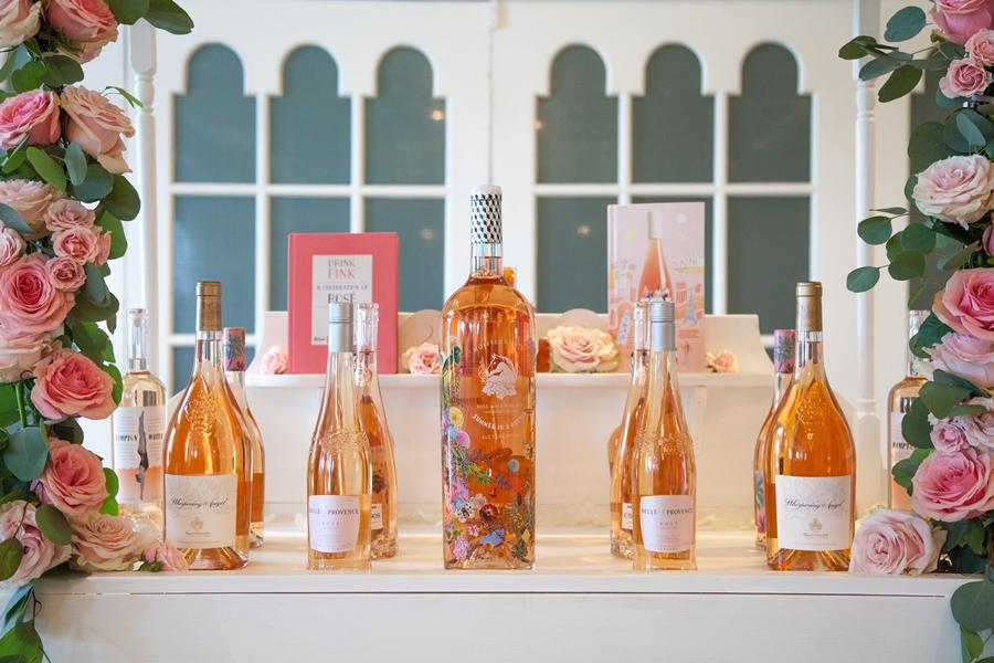 bottles of rose wine framed by floral garland