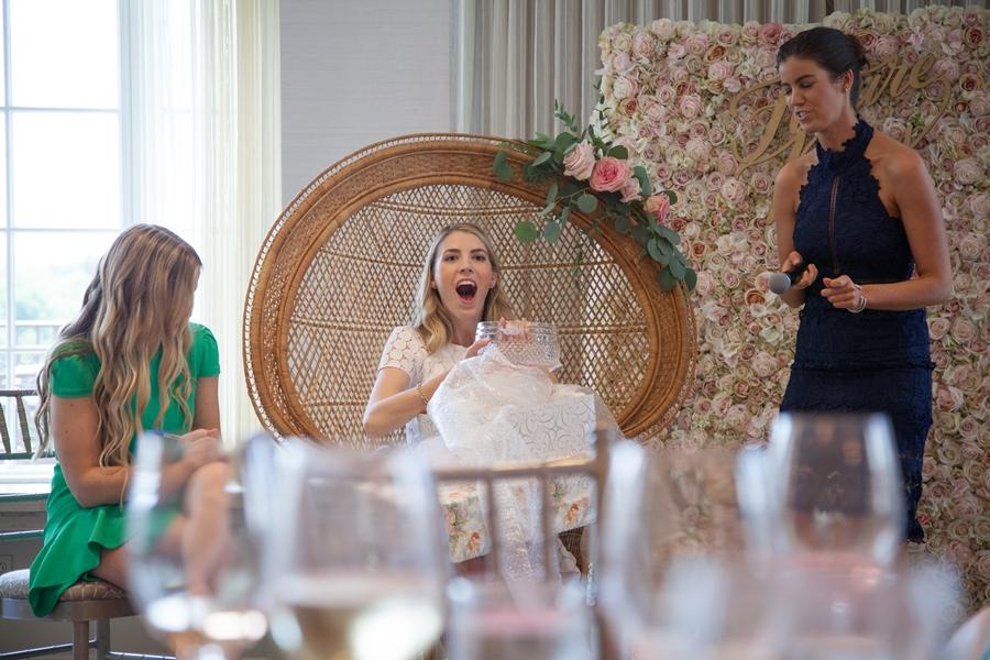 bride opens gifts at bridal shower