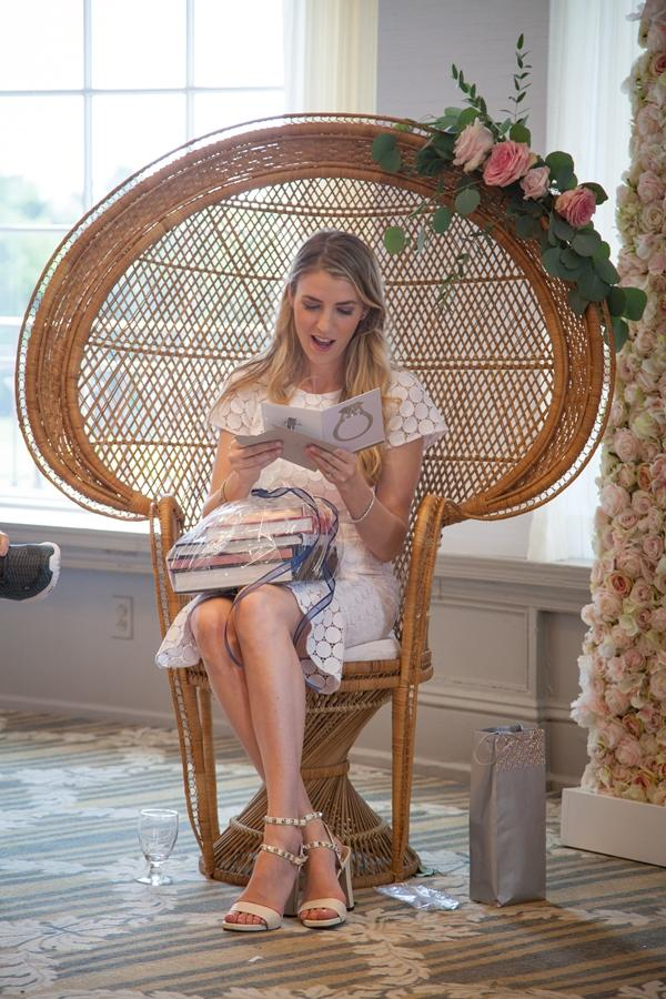 bride reads card and sits in rattan peacock  chair