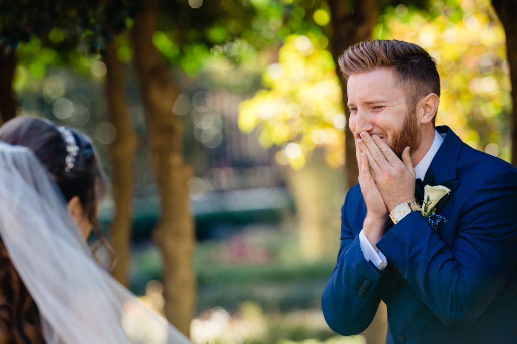 emotional groom looks at bride