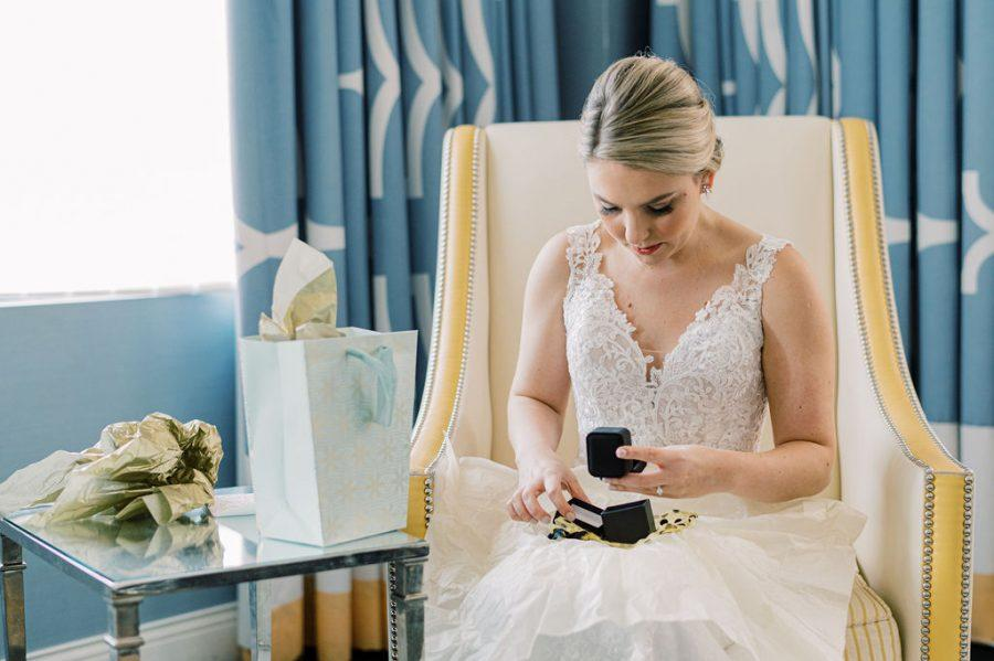 bride opens gift from groom on her wedding day
