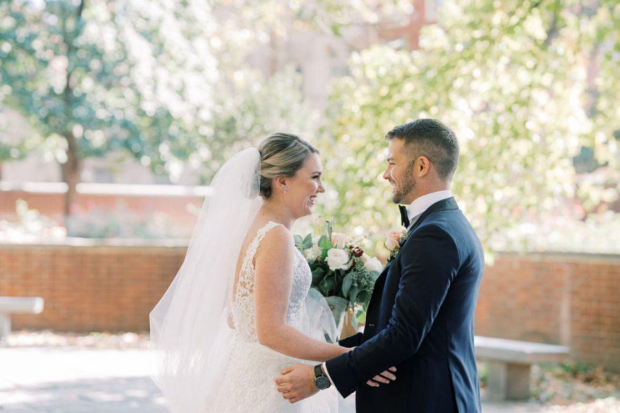 bride and groom embrace in outdoor courtyard
