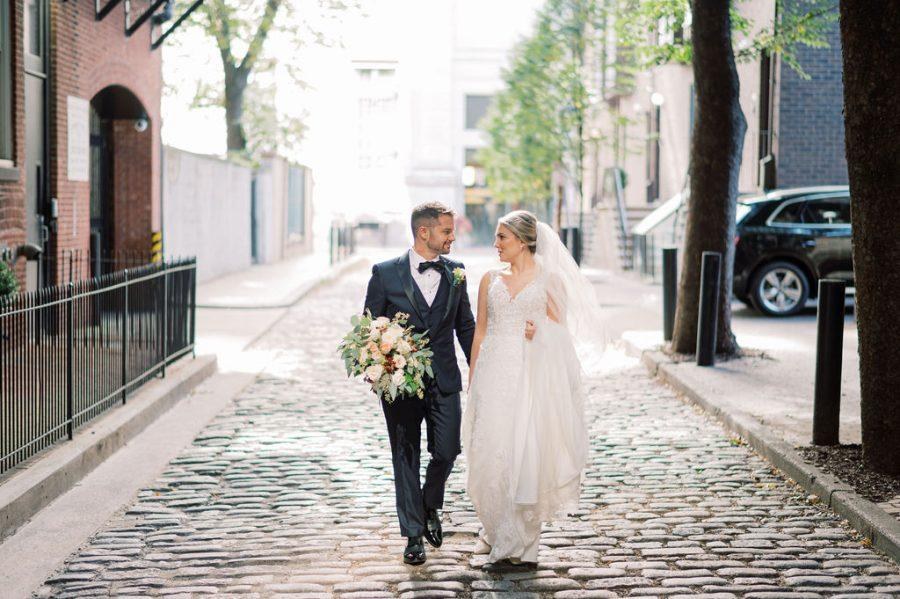 bride and groom hold hands while walking down cobblestone street