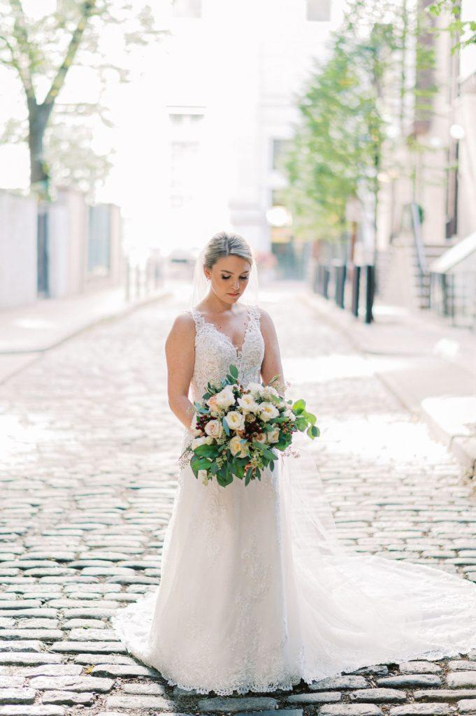 bride wearing wedding gown posing on cobblestone street