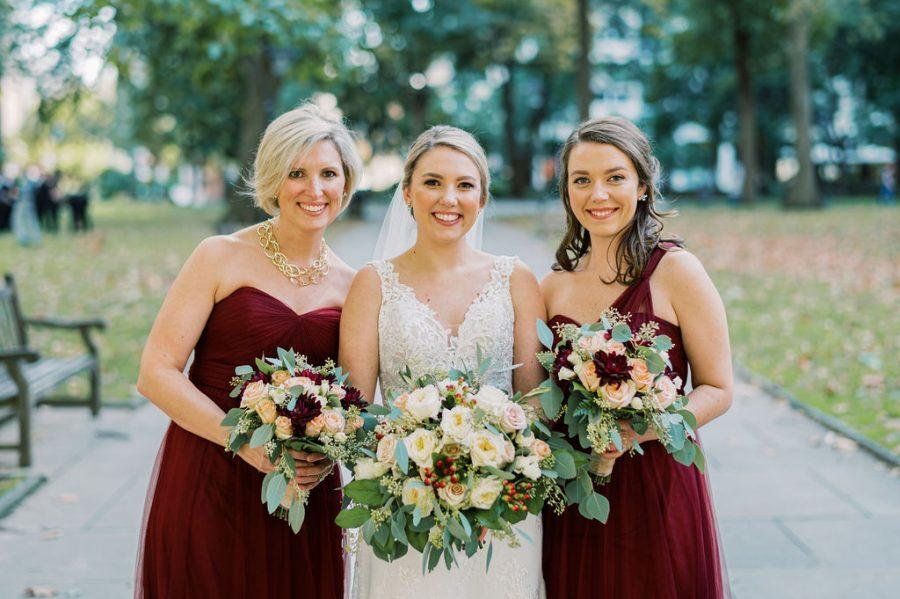 bride and bridesmaids pose in city square