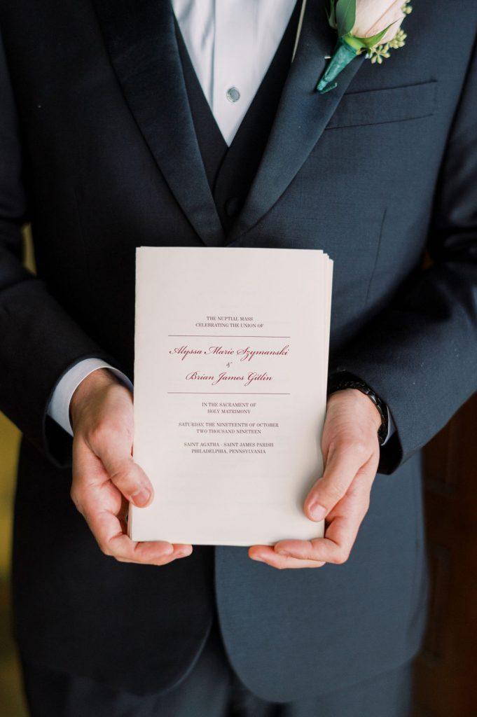 groom holding wedding invitation