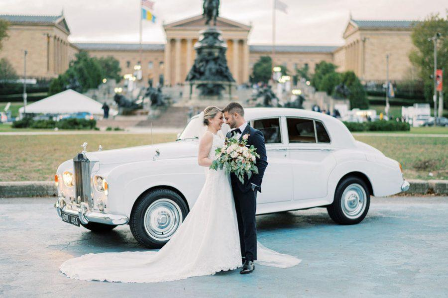 bride and groom pose in front of rolls royce outside Philadelphia museum of art