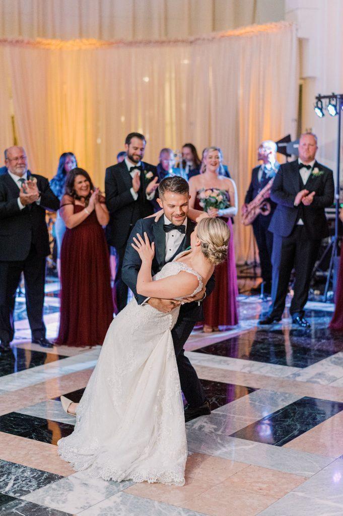 groom dips bride on dance floor