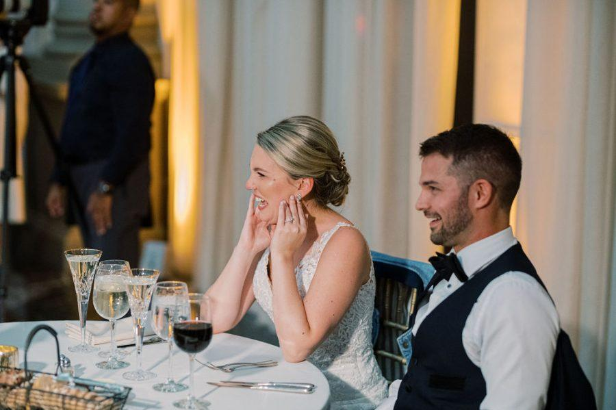 bride and groom sit at sweetheart table