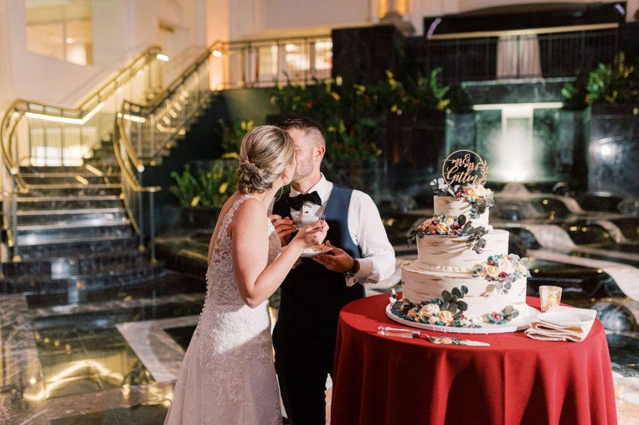 couple kiss while cutting wedding cake