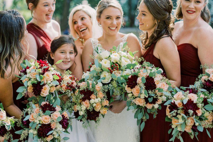 bride and bridesmaids holding burgundy, green and yellow bouquets
