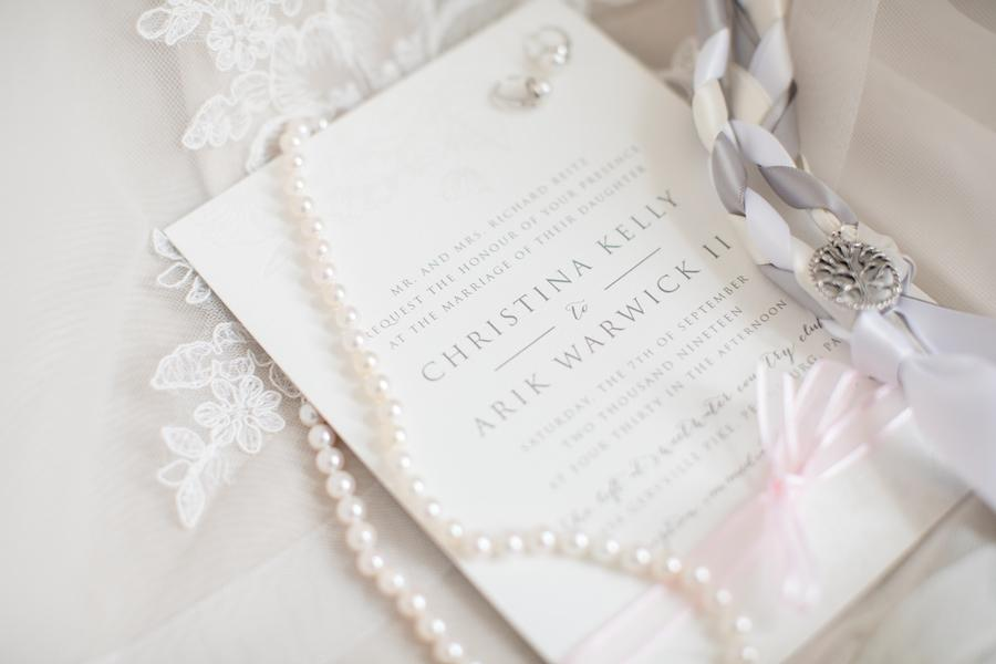 white wedding invitation and pearls