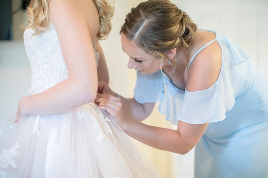 bridesmaid helps bride into wedding dress