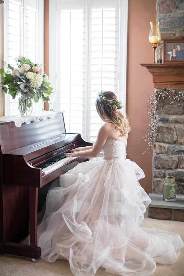 bride plays piano in wedding dress