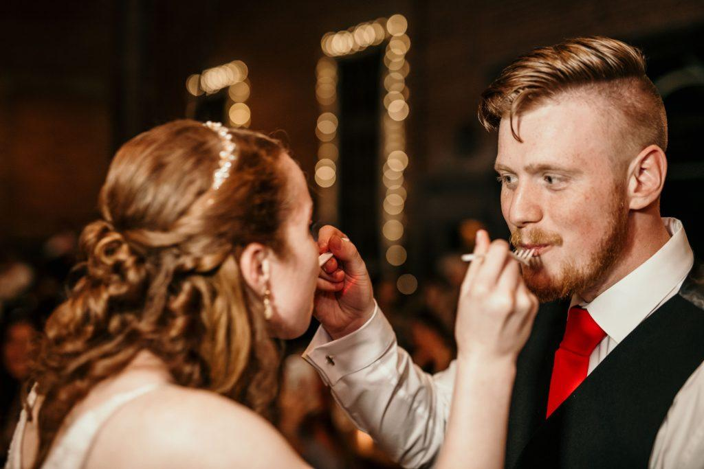 bride and groom feed each other wedding cake