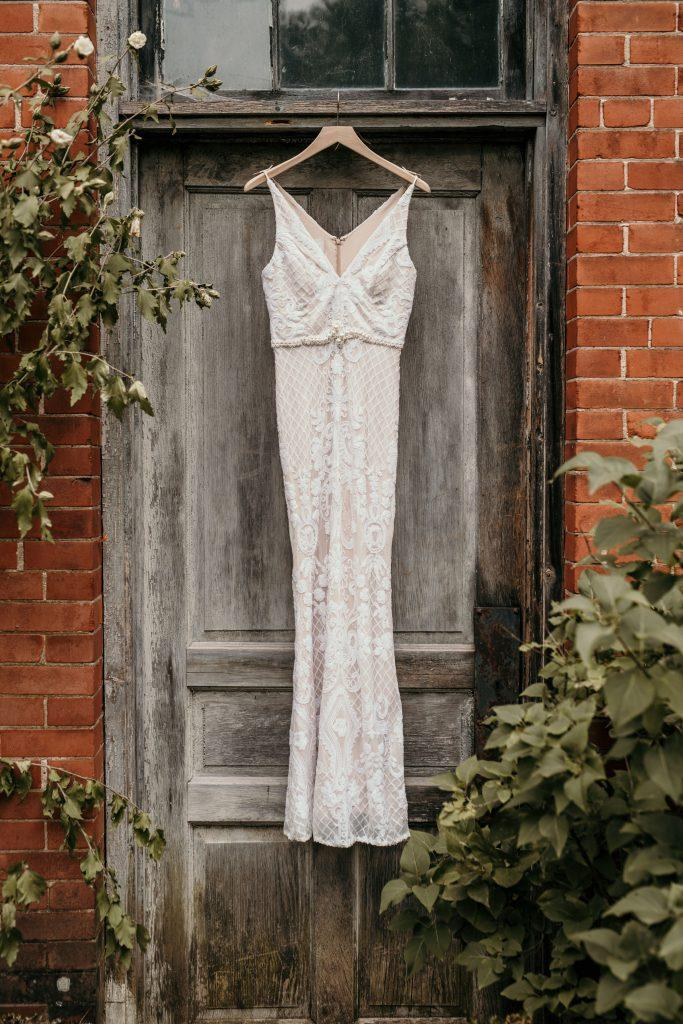 lace wedding dress hanging on wooden door outside