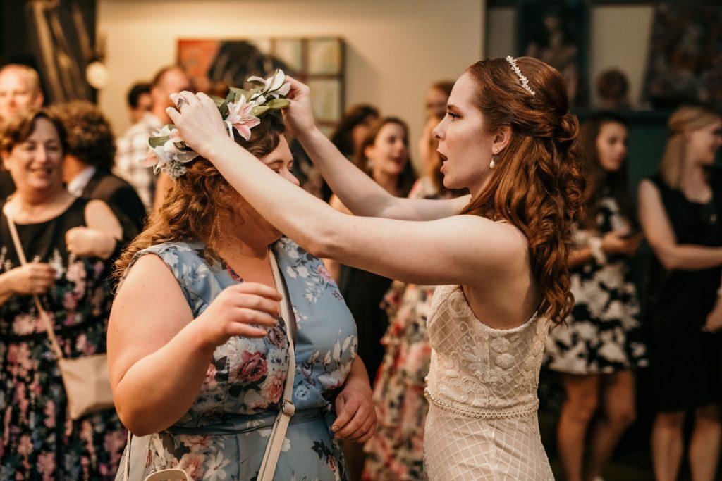 bride places floral crown on wedding guest