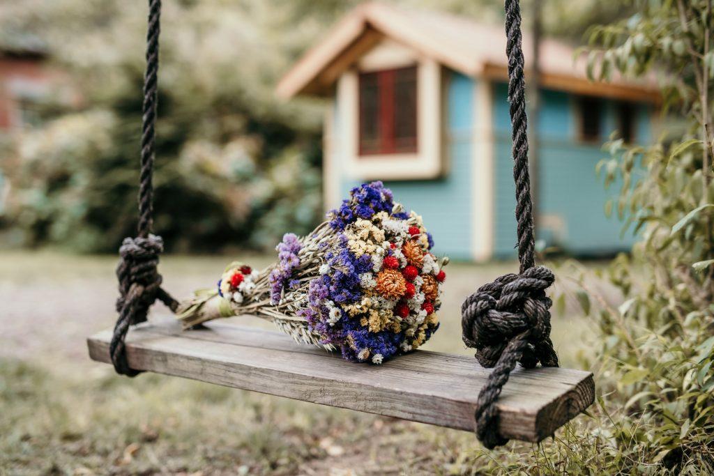 dried flower bouquet on wooden swing