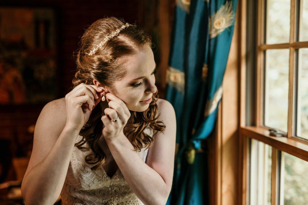 bride putting on pearl earrings