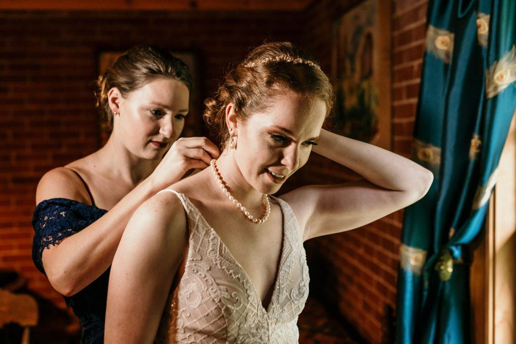 maid of honor puts on bride's pearl necklace