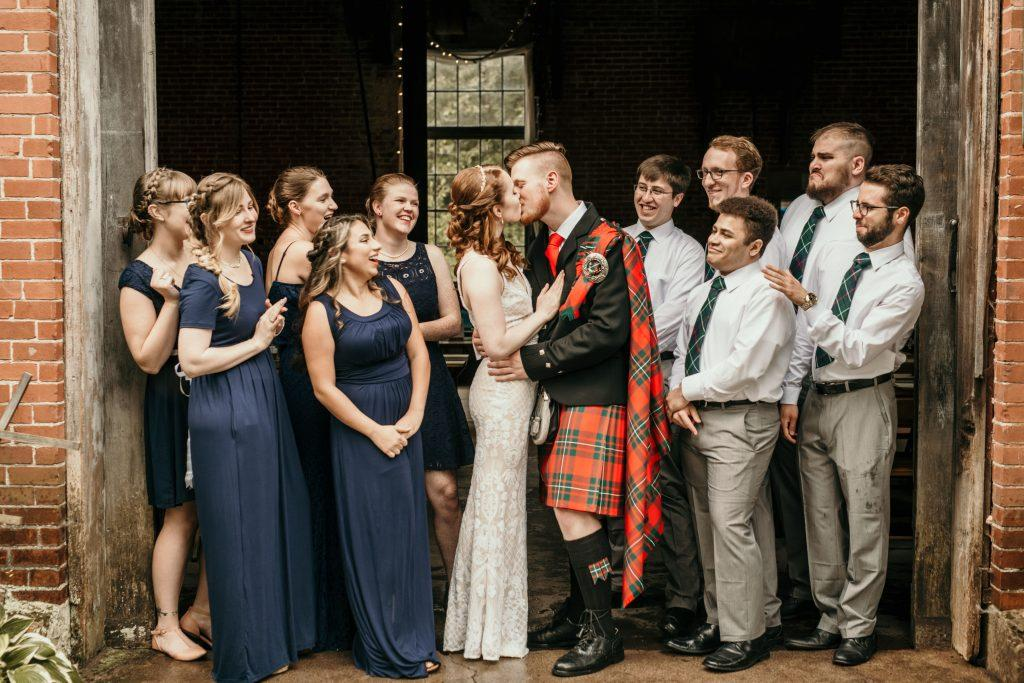 bride, groom and bridal party pose in front of barn
