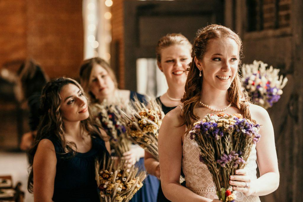 bride standing at altar with bridesmaids holding bouquet