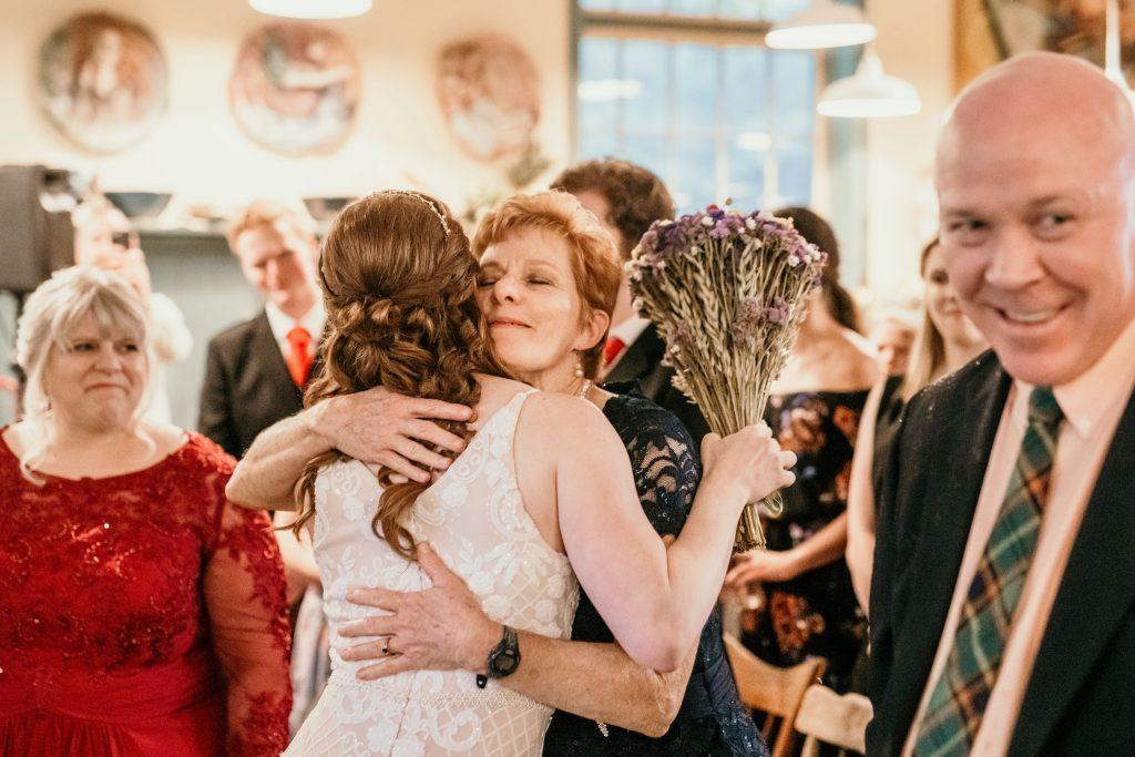 bride hugs mom at wedding