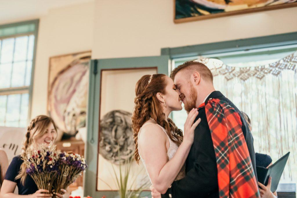 bride and groom share first wedding kiss