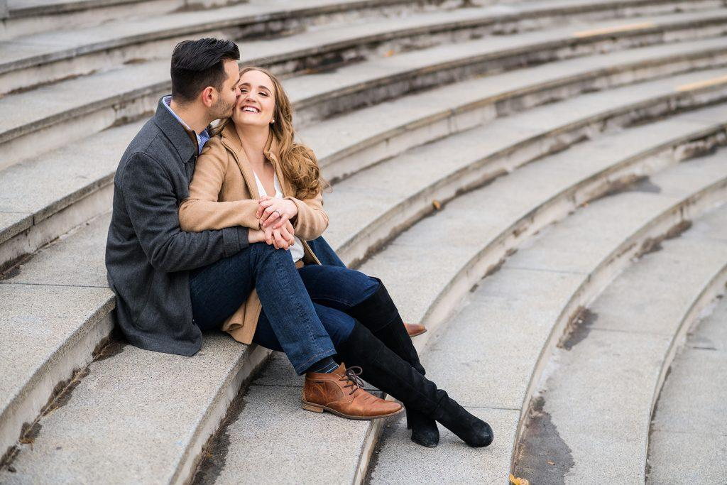 engaged couple kiss on outdoor stairs