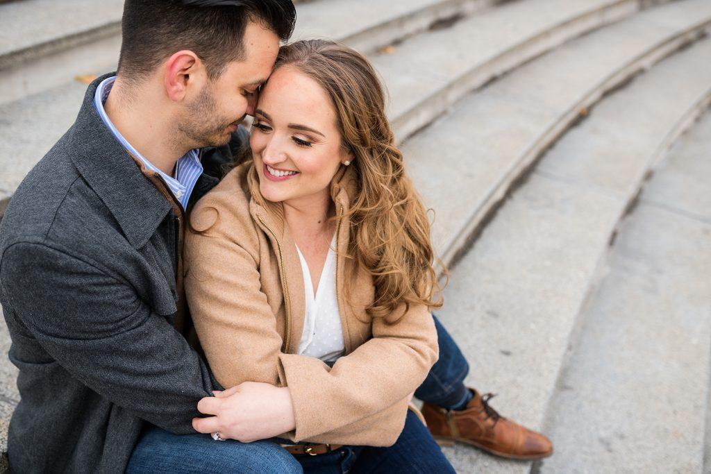 engaged couple sit on steps