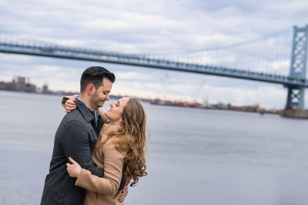 engaged couple hug on pier in front of bridge