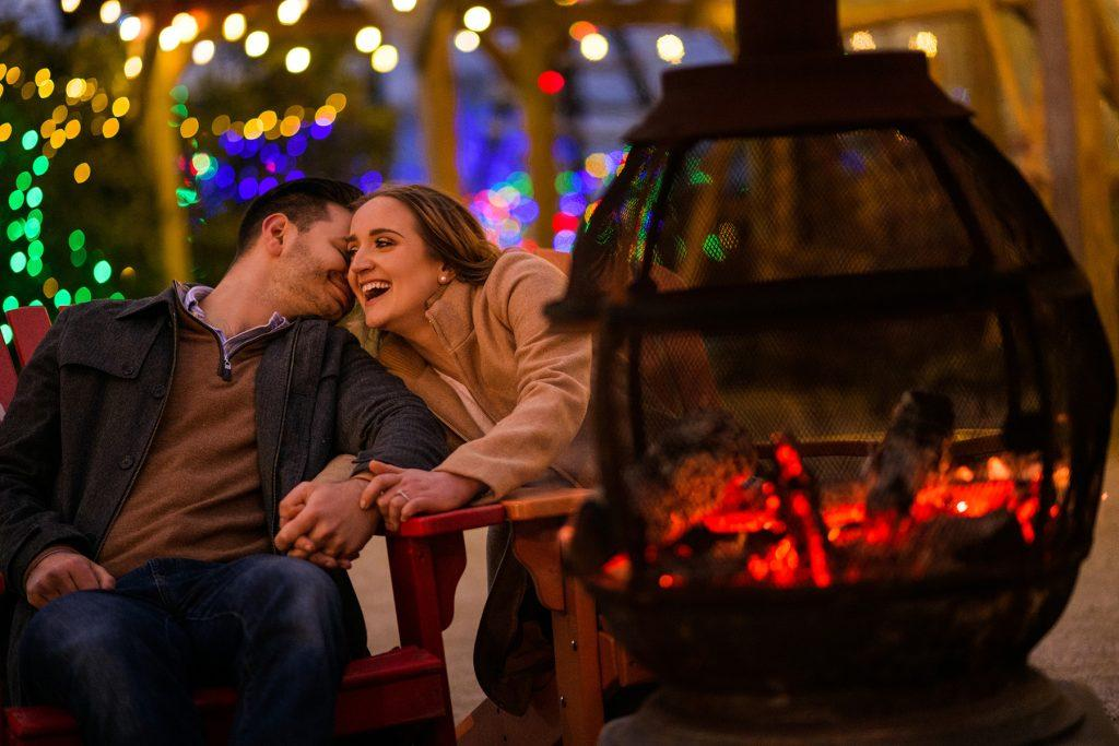 couple sit by outdoor fireplace