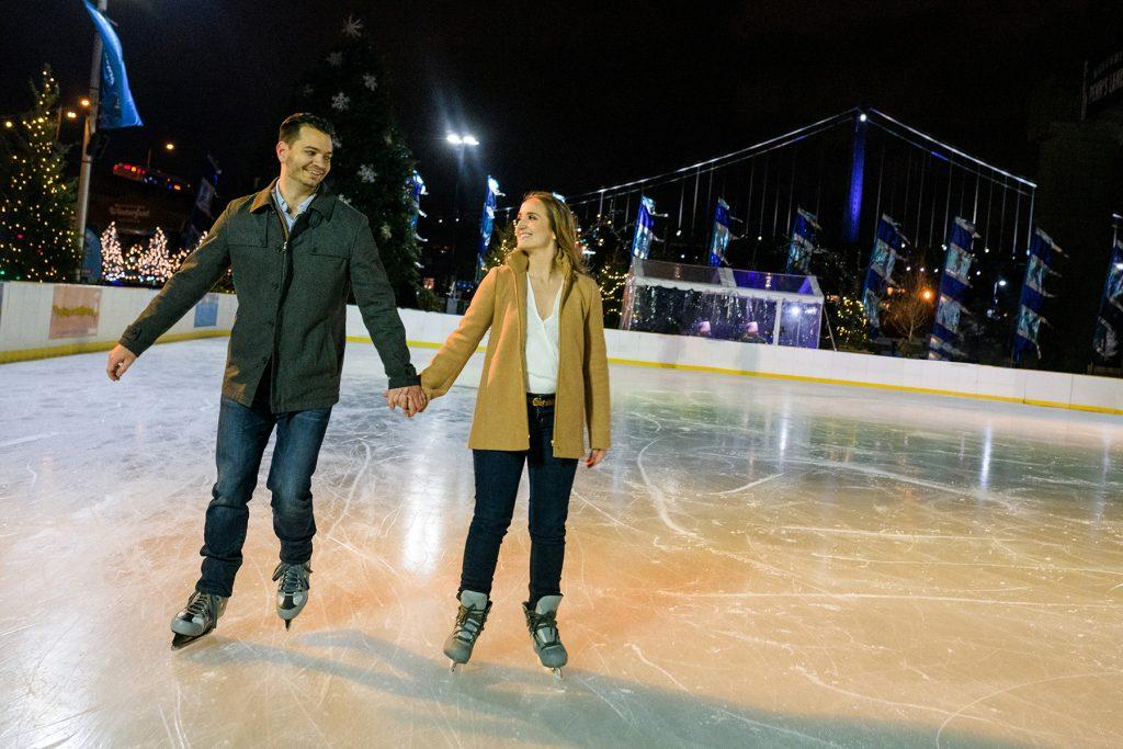 engaged couple hold hands while ice skating