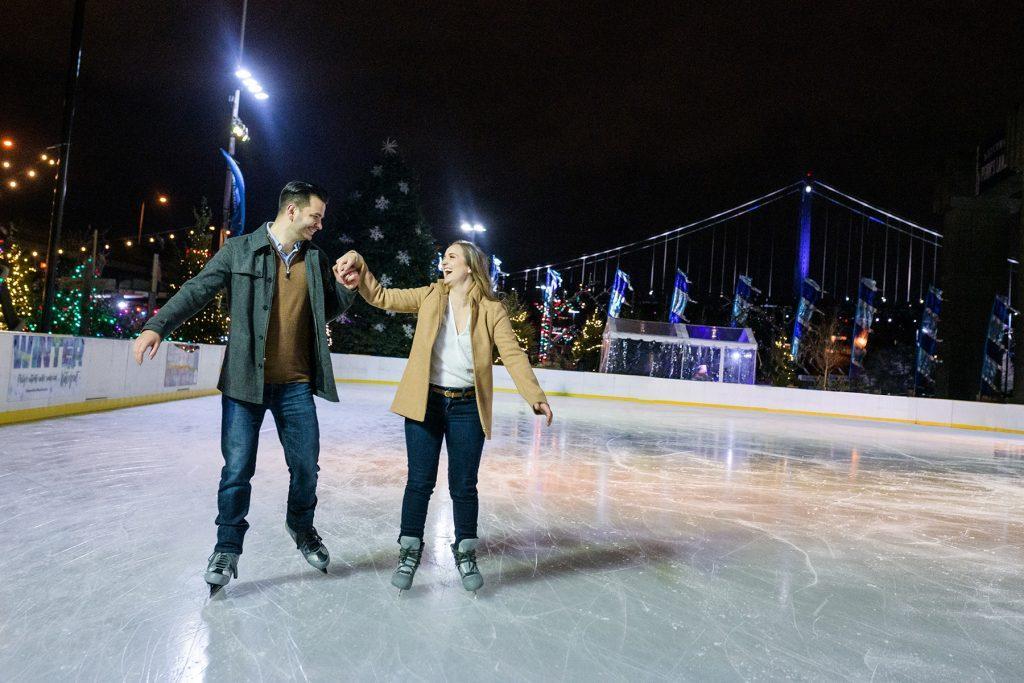 engaged couple ice skating at night
