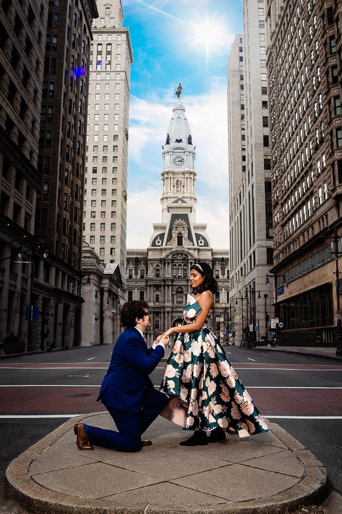 man on one knee with fiance in front of city hall