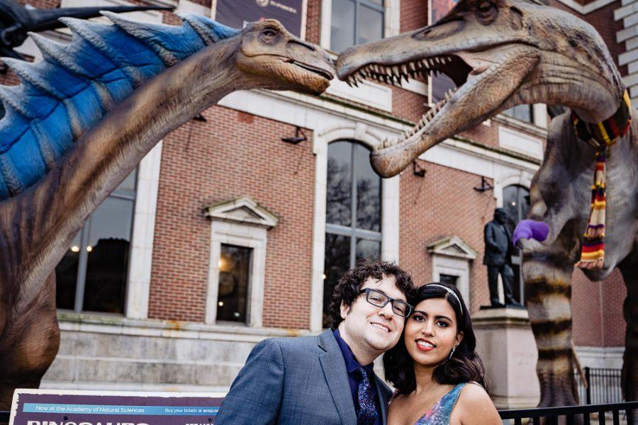 couple pose in front of dinosaurs