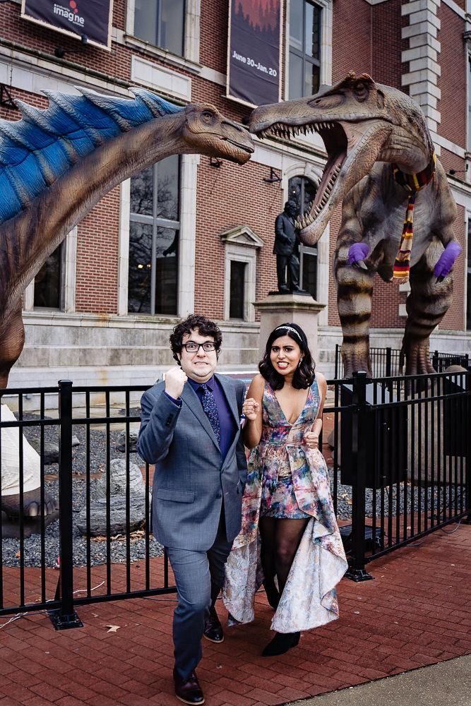 couple pretending to be superheros in front of dinosaurs