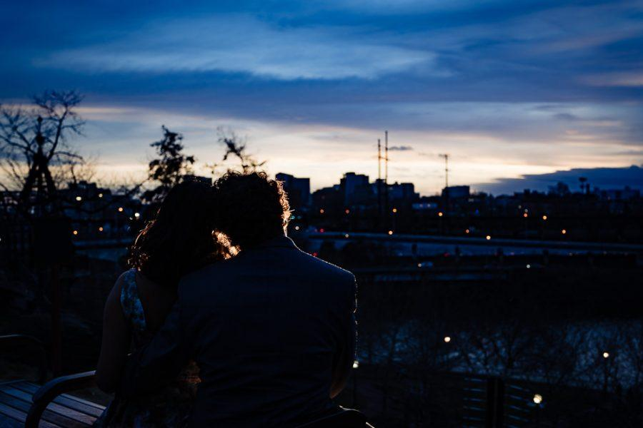 couple embrace at night overlooking river