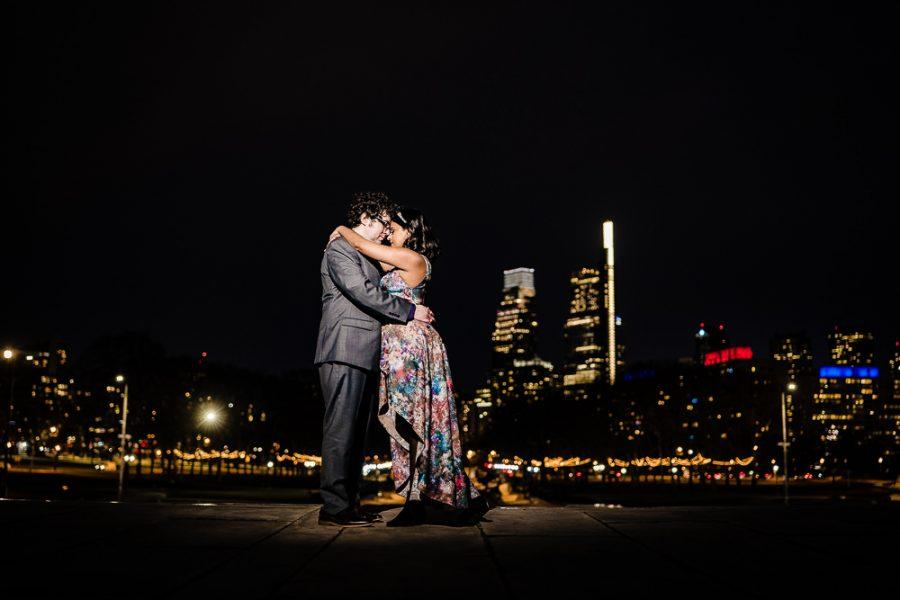 couple embrace at night in front of city skyline