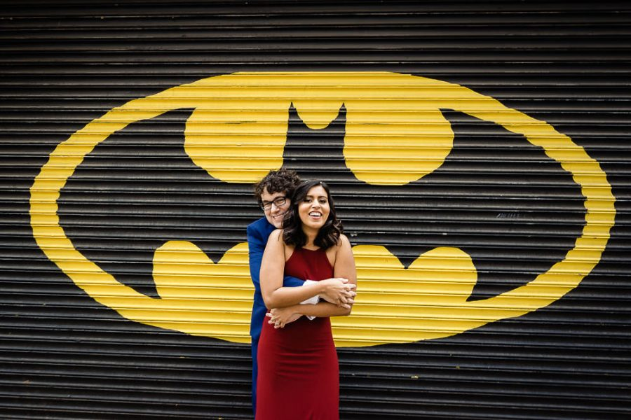 couple pose in front of Batman insignia